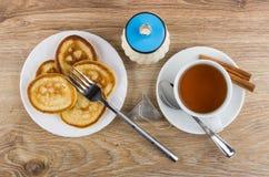 Τηγανίτες, δίκρανο, φλυτζάνι του τσαγιού, κανέλα, ζάχαρη και κουταλάκι του γλυκού Στοκ Εικόνες