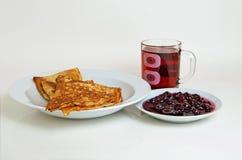 Τηγανίτες και μαρμελάδα κερασιών με το τσάι για το πρόγευμα Στοκ Εικόνες