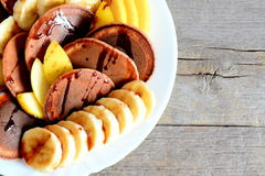 Τηγανίτες κακάου με τους νωπούς καρπούς Ψημένες τηγανίτες κακάου με το σιρόπι, τις τεμαχισμένα μπανάνες και τα μήλα σε ένα άσπρο  Στοκ Εικόνα