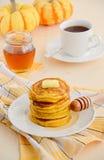 Τηγανίτες κολοκύθας στο άσπρο πιάτο με το βούτυρο και το μέλι Στοκ Φωτογραφία