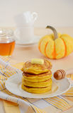 Τηγανίτες κολοκύθας στο άσπρο πιάτο με το βούτυρο και το μέλι Στοκ Φωτογραφίες