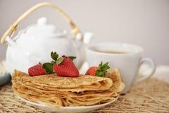 Τηγανίτες με μια φράουλα και ένα καυτό τσάι teapot και το φλυτζάνι Στοκ Εικόνες