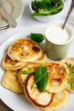 Τηγανίτες με τα μανιτάρια και τα κρεμμύδια, που εξυπηρετούνται με την ξινή κρέμα και μια πράσινη σαλάτα Στοκ φωτογραφίες με δικαίωμα ελεύθερης χρήσης