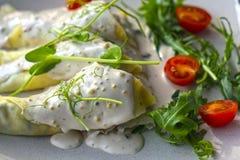 Τηγανίτες με τα μανιτάρια σε μια σάλτσα που διακοσμείται με τα πράσινα και τις ντομάτες στοκ φωτογραφία