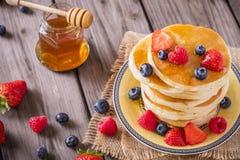 Τηγανίτες με τα μούρα και το μέλι Στοκ φωτογραφία με δικαίωμα ελεύθερης χρήσης