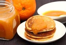 Τηγανίτες με τα πορτοκάλια και πορτοκαλιά μαρμελάδα στο βάζο γυαλιού Στοκ εικόνες με δικαίωμα ελεύθερης χρήσης