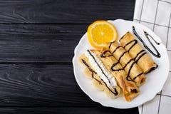 Τηγανίτες με την μπανάνα, κτυπημένη κρέμα που διακοσμείται με το σιρόπι σοκολάτας στο μαύρο ξύλινο υπόβαθρο Τοπ άποψη με το διάστ Στοκ Φωτογραφίες