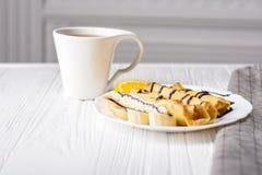 Τηγανίτες με την μπανάνα, την κτυπημένη κρέμα που διακοσμούνται με το σιρόπι σοκολάτας στο άσπρο ξύλινο υπόβαθρο και το φλυτζάνι  Στοκ φωτογραφίες με δικαίωμα ελεύθερης χρήσης