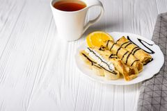 Τηγανίτες με την μπανάνα, την κτυπημένη κρέμα που διακοσμούνται με το σιρόπι σοκολάτας στο άσπρο ξύλινο υπόβαθρο και το φλυτζάνι  Στοκ εικόνες με δικαίωμα ελεύθερης χρήσης