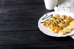 Τηγανίτες με την μπανάνα που διακοσμείται με το σιρόπι σοκολάτας στο μαύρο ξύλινο υπόβαθρο με το διάστημα αντιγράφων Στοκ Εικόνες