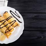 Τηγανίτες με την μπανάνα που διακοσμείται με το σιρόπι σοκολάτας στο μαύρο ξύλινο υπόβαθρο Τοπ άποψη με το διάστημα αντιγράφων Στοκ εικόνες με δικαίωμα ελεύθερης χρήσης