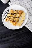 Τηγανίτες με την μπανάνα που διακοσμείται με το σιρόπι σοκολάτας στο μαύρο ξύλινο υπόβαθρο Τοπ άποψη με το διάστημα αντιγράφων Στοκ Εικόνες