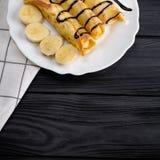 Τηγανίτες με την μπανάνα που διακοσμείται με το σιρόπι σοκολάτας στο μαύρο ξύλινο υπόβαθρο Τοπ άποψη με το διάστημα αντιγράφων Στοκ εικόνα με δικαίωμα ελεύθερης χρήσης