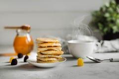 Τηγανίτες με το μέλι και ένα φλυτζάνι του τσαγιού στοκ εικόνα