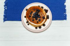 Τηγανίτες με το μέλι και βακκίνια σε μια μπλε πετσέτα Στοκ εικόνα με δικαίωμα ελεύθερης χρήσης