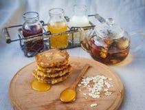 Τηγανίτες με το μέλι σε έναν ξύλινους πίνακα και ένα τσάι Στοκ Φωτογραφίες