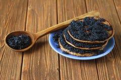 Τηγανίτες με το μαύρο χαβιάρι σε ένα πιάτο, ένα ξύλινο κουτάλι στον πίνακα Στοκ φωτογραφία με δικαίωμα ελεύθερης χρήσης