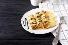Τηγανίτες με το τυρί εξοχικών σπιτιών και μια μπανάνα με το σιρόπι σοκολάτας Στοκ Φωτογραφίες