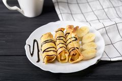 Τηγανίτες με το τυρί εξοχικών σπιτιών και μια μπανάνα με το σιρόπι σοκολάτας Στοκ φωτογραφία με δικαίωμα ελεύθερης χρήσης