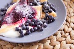 Τηγανίτες με το τυρί, την κρέμα και τα βακκίνια Στοκ φωτογραφία με δικαίωμα ελεύθερης χρήσης