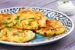 Τηγανίτες πατατών με τη σάλτσα γιαουρτιού Φυτικά fritters Latkes στο μπλε πιάτο Στοκ φωτογραφίες με δικαίωμα ελεύθερης χρήσης