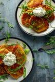 Τηγανίτες πατατών, draniki, hash - Browns ή fritters που εξυπηρετείται με φρέσκια άγρια σαλάτα φύλλων πυραύλων Στοκ Εικόνα