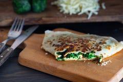 Τηγανίτες που γεμίζουν με το σπανάκι και το τυρί στην ξύλινη επιφάνεια Στοκ Φωτογραφίες