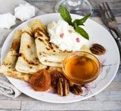 Τηγανίτες προγευμάτων, μέλι, μαρμελάδα φραουλών, κρέμα, ξηρά βερίκοκα, καρύδια και καυτό σοκολάτα ή κακάο ή καφές στοκ φωτογραφίες με δικαίωμα ελεύθερης χρήσης