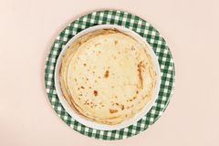 Τηγανίτες σε ένα πιατάκι σε μια πετσέτα κουζινών Πολλές τηγανίτες συσσωρεύονται Λεπτές τηγανίτες με την τριζάτη κρούστα Maslenits στοκ φωτογραφία με δικαίωμα ελεύθερης χρήσης