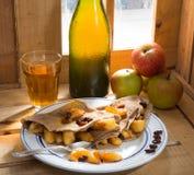 Τηγανίτες της Apple με ένα μπουκάλι και ένα ποτήρι του μηλίτη Στοκ Εικόνες