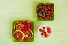 Τηγανίτες τυριών εξοχικών σπιτιών με τα φρέσκα σμέουρα, το κεράσι και την ξινή κρέμα στα πράσινα πιάτα στο πράσινο ξύλινο υπόβαθρ Στοκ Φωτογραφία