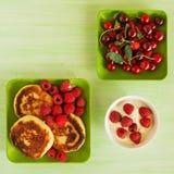 Τηγανίτες τυριών εξοχικών σπιτιών με τα φρέσκα σμέουρα, το κεράσι και την ξινή κρέμα στα πράσινα πιάτα στο πράσινο ξύλινο υπόβαθρ Στοκ Εικόνες