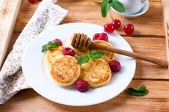 Τηγανίτες τυριών εξοχικών σπιτιών με το μέλι στο υπόβαθρο Στοκ Φωτογραφίες