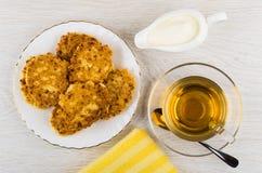 Τηγανίτες τυριών εξοχικών σπιτιών στο πιάτο, κουταλάκι του γλυκού, φλυτζάνι του τσαγιού Στοκ φωτογραφίες με δικαίωμα ελεύθερης χρήσης