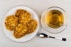 Τηγανίτες τυριών εξοχικών σπιτιών στο πιάτο, κουταλάκι του γλυκού, φλυτζάνι του τσαγιού Στοκ Φωτογραφία