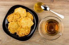 Τηγανίτες τυριών εξοχικών σπιτιών στο πιάτο, κύπελλο του μελιού, κουταλάκι του γλυκού, τσάι Στοκ φωτογραφία με δικαίωμα ελεύθερης χρήσης