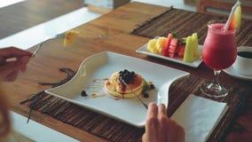 Τηγανίτες, φρούτα, χυμός και καφές βακκινίων στον ξύλινο πίνακα φιλμ μικρού μήκους