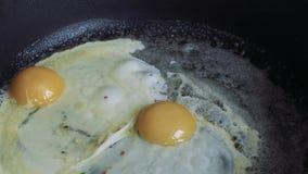 Τηγανητά αυγών κοτόπουλου στο βούτυρο σε ένα τηγάνι απόθεμα βίντεο