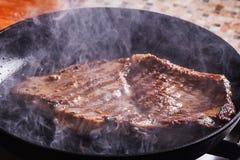 Τηγανητά μπριζόλας βόειου κρέατος στον καπνό και τον ατμό Στοκ φωτογραφία με δικαίωμα ελεύθερης χρήσης