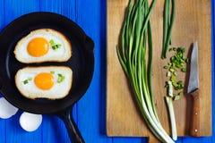 Τηγανισμένα αυγά και κρεμμύδι άνοιξη στο μπλε ξύλινο υπόβαθρο Στοκ εικόνες με δικαίωμα ελεύθερης χρήσης