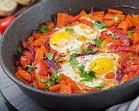 Τηγανισμένα αυγά με τα κομμάτια της κολοκύθας, των κόκκινων κρεμμυδιών και των ντοματών Στοκ Εικόνα