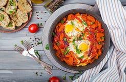 Τηγανισμένα αυγά με τα κομμάτια της κολοκύθας, των κόκκινων κρεμμυδιών και των ντοματών Στοκ Φωτογραφίες