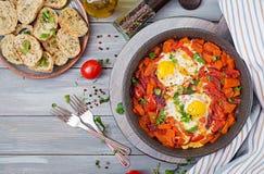 Τηγανισμένα αυγά με τα κομμάτια της κολοκύθας, των κόκκινων κρεμμυδιών και των ντοματών Στοκ φωτογραφία με δικαίωμα ελεύθερης χρήσης