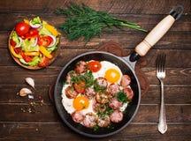 Τηγανισμένα αυγά με το λουκάνικο και ντομάτες στο τηγάνισμα του τηγανιού που εξυπηρετείται με το s Στοκ φωτογραφία με δικαίωμα ελεύθερης χρήσης