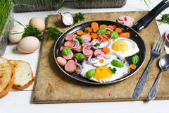 Τηγανισμένα αυγά σε ένα τηγανίζοντας τηγάνι με τα λαχανικά Στοκ Φωτογραφία