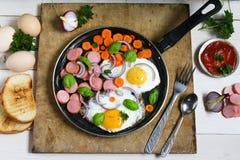 Τηγανισμένα αυγά σε ένα τηγανίζοντας τηγάνι με τα λαχανικά Στοκ Φωτογραφίες