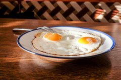 Τηγανισμένα αυγά στο δίσκο με την ανοικτό μπλε πιατέλα Στοκ Φωτογραφία