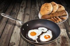 Τηγανισμένα αυγά στο παλαιό τεφλόν τηγανίζοντας τηγάνι με Plateful των φετών Baguette και των φραντζολών ψωμιού Pitta που τίθεντα Στοκ Εικόνες