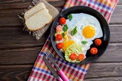 Τηγανισμένα αυγά στο τηγάνι με την ντομάτα, το ψωμί, το πιπέρι και το μαϊντανό Στοκ εικόνες με δικαίωμα ελεύθερης χρήσης