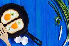 τηγανισμένα αυγά, τριζάτα φρυγανιά και κρεμμύδι άνοιξη στον μπλε ξύλινο πίνακα Στοκ Εικόνα